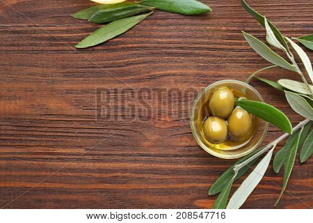 Glass bowl with olive oil on wooden table