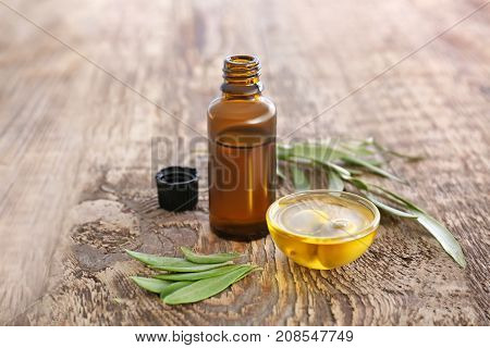 Brown bottle and glass bowl with olive oil on wooden table