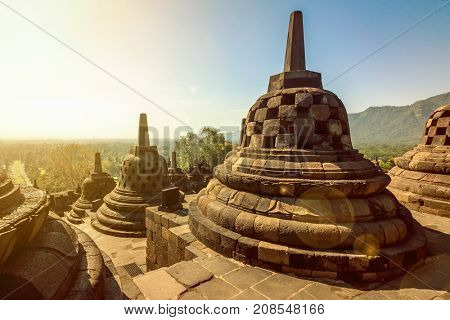 Buddist temple Borobudur complex in Yogjakarta in Java, Indonesia. With lens flare and light leak
