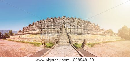Panorama Buddist temple Borobudur complex in Yogjakarta in Java, Indonesia. With lens flare and light leak