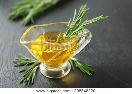 Gravy boat with rosemary oil and herb on wooden table