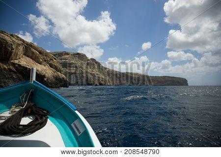 Malta, rocky sea shore from a small boat on sea