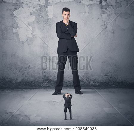 Big angry business bully looking at small coworker concept on background