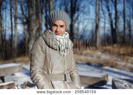 Portrait of smiling woman walking in forest in winter wearing hat scarf and warm coat.