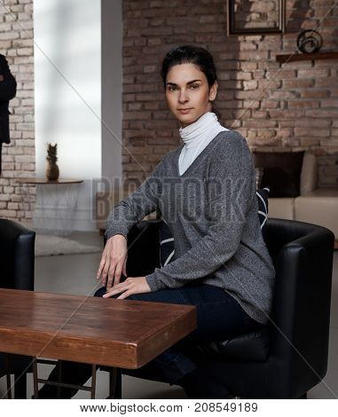 Portrait of attractive young confident businesswoman sitting, looking at camera.