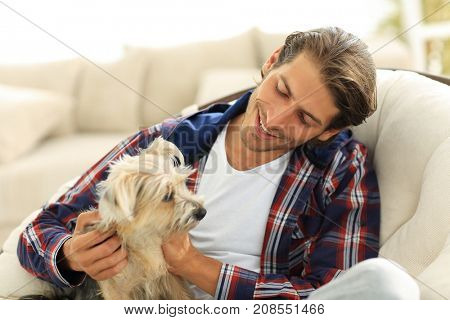 handsome guy stroking his dog while sitting in a large armchair.