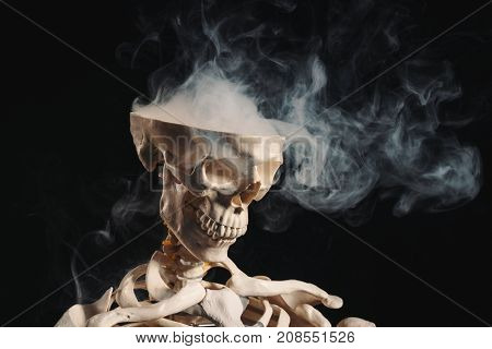 Skeleton with smoke coming out of open skull, open mind concept