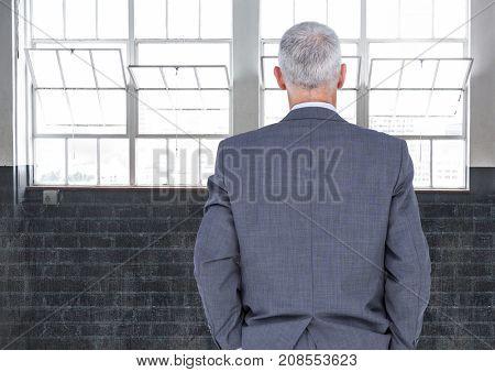 Digital composite of Businessman looking at windows