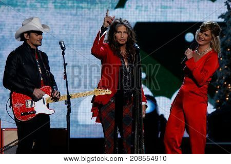 NASHVILLE, TN-NOV 7: Singers Brad Paisley (L), Steven Tyler and Jennifer Nettles speak onstage at the 2014 CMA Country Christmas at the Bridgestone Arena on November 7, 2014 in Nashville, Tennessee.