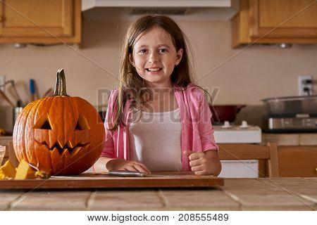 proud little girl standing beside jack-o-lantern pumpkin in kitchen