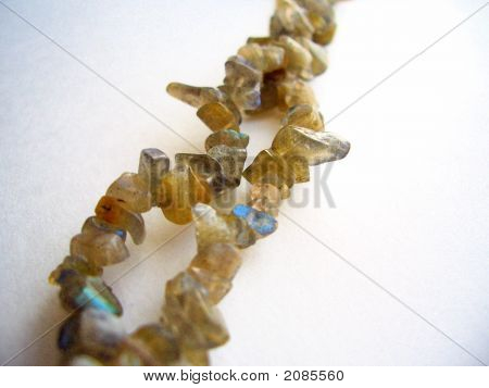 Photo shows assorted multicolor labradorite beads nugget and irregular shapes on double strand of string. Colors include brown tan iridescent amber grey blue earth tones. poster