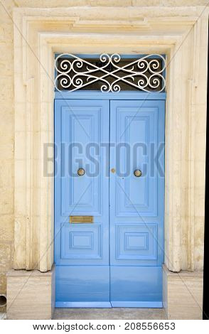 Light blue wooden entrance door with ornated sign and knocker