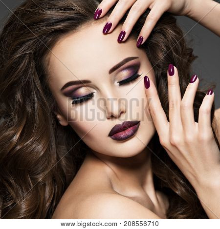 Beautiful face of  young woman with maroon makeup. Portrait of gorgeous girl with vinous nails
