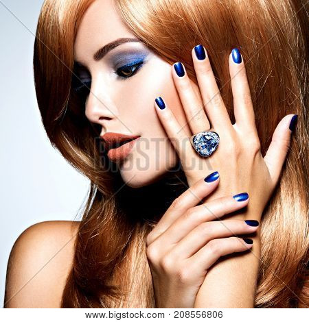 portrait of a beautiful woman with blue nails, blue makeup and red hairs at studio