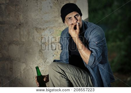 Man sitting with cigarette and bottle of alcohol in abandoned building