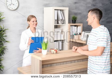 Young female receptionist with client in hospital