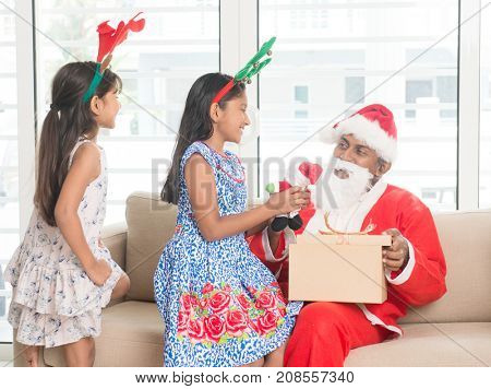 Happy Indian family celebrating Christmas holidays, with gift box and santa sitting on couch at home, Asian people festival mood indoors.