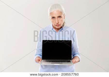 Displeased sad mature woman in blue shirt holding laptop computer with blank screen isolated over white