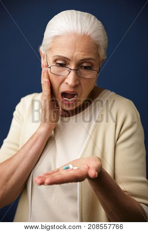 Image of old shocked woman over dark blue background looking at pills.