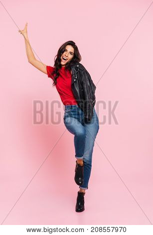 Full length image of carefree brunette woman posing in studio and showing peace sign while looking at the camera over pink background