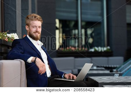 Handsome young man with laptop, outdoors