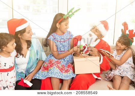 Happy Asian Indian family celebrating Christmas holidays, with gift box and santa sitting on sofa or couch at home, parents and children festival mood indoors.
