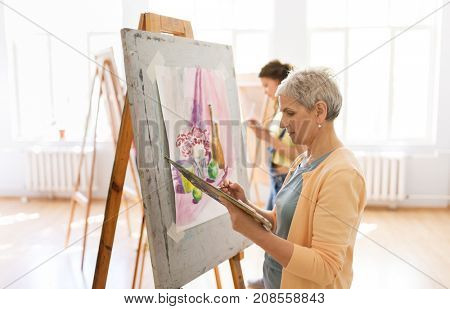 art school, creativity and people concept - senior woman artist with easel, paint brush and palette painting at studio