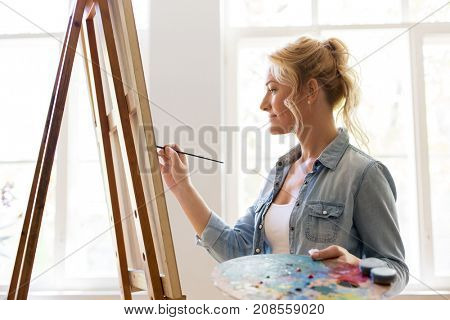 art school, creativity and people concept - happy smiling woman artist with easel, paint brush and palette painting at studio