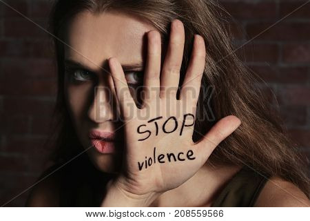 Woman with written text STOP VIOLENCE on palm