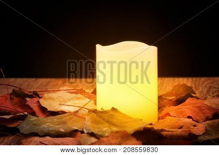 Brightly burning candle surrounded by autumn leaves on dark background