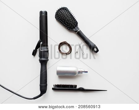 hair tools and hairdressing concept - curling iron, brushes, hot styling spay, ties and clips on white background