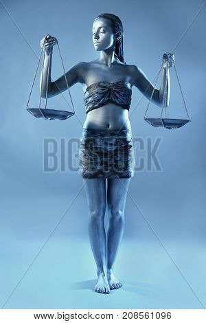 Beautiful young woman with amazing bodyart as Libra on color background. Zodiac signs concept