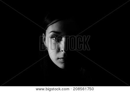 Black and white photo of the Beautiful woman face in the darkness