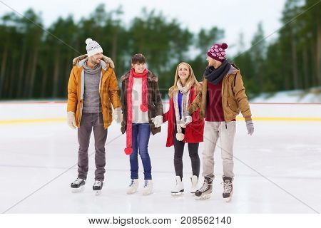 friendship, sport and leisure concept - happy friends holding hands on skating rink over outdoor background