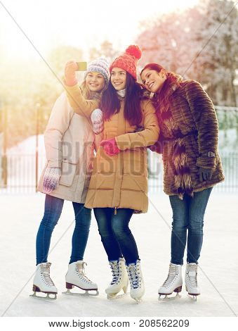 people, friendship, technology and leisure concept - happy girl friends taking selfie with smartphone on ice skating rink outdoors