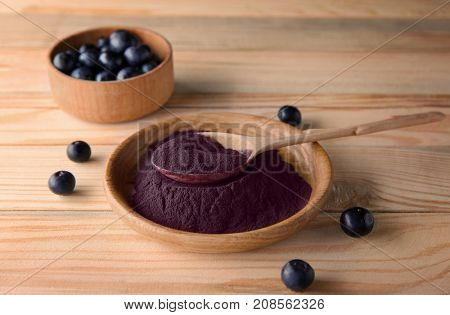 Acai powder and berries in kitchenware on wooden background
