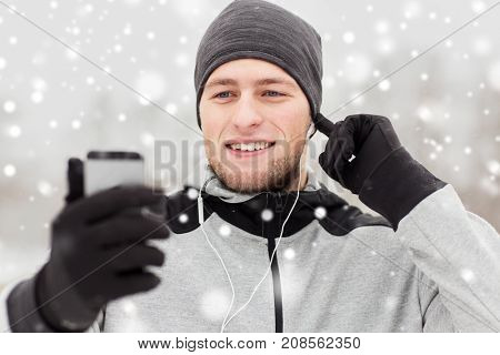 fitness, sport, people, technology and healthy lifestyle concept - happy smiling young man in earphones with smartphone listening to music on winter bridge