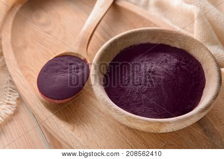 Spoon and bowl with acai powder on wooden tray