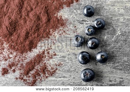 Acai berries and powder on grey background