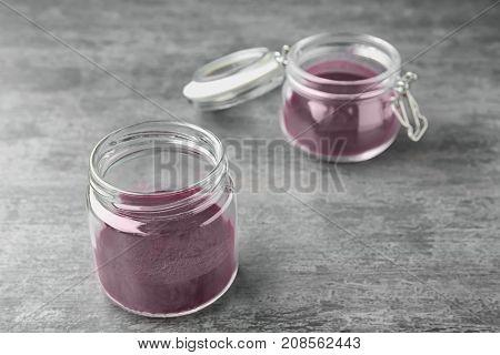 Glass jars with acai powder on grey background
