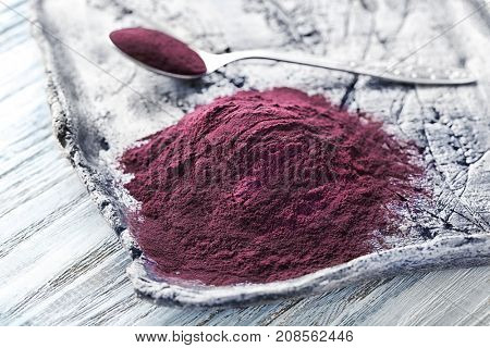 Tray with acai powder on wooden background