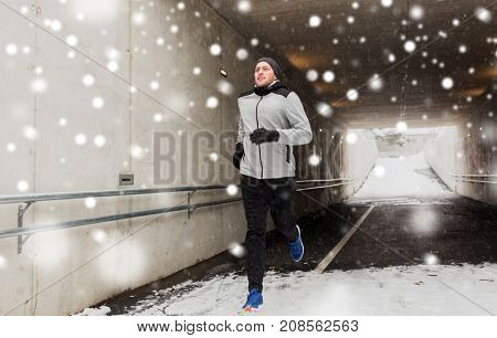 fitness, sport, people, season and healthy lifestyle concept - happy young man running along pedestrian subway tunnel in winter