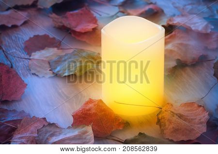 Brightly burning candle in fog on wooden table with autumn leaves. Tinted under cool autumn evening