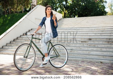 Full length portrait of a smiling cheerful girl holding mobile phone while riding on a bicycle and looking away outdoors