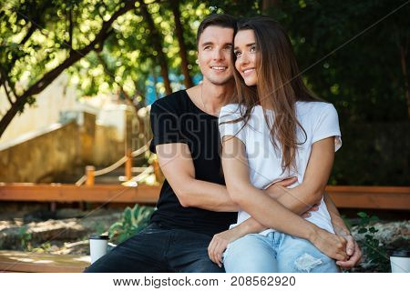 Portrait of a smiling attractive couple in love sitting on the bench and hugging at the park outdoors