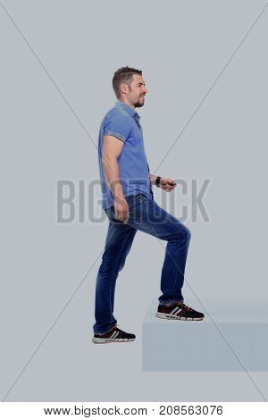 Casual man up the staircase over white background
