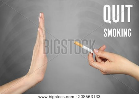 Text QUIT SMOKING and woman refusing of offered cigarette on grey background