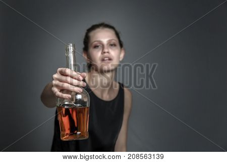 Drunk woman with bottle of alcohol drink on grey background