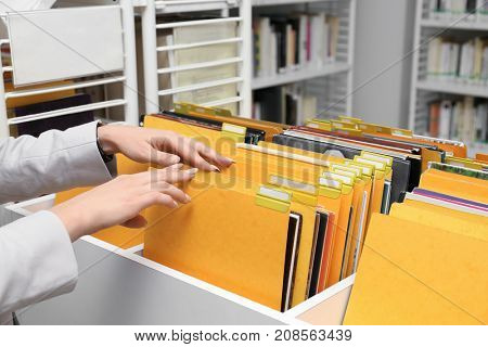 Woman searching for documents in archive