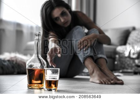 Drunk woman reaching after glass and bottle of alcohol drink on floor